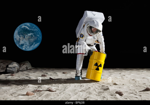 An astronaut rolling a drum of toxic material on the moon surface - Stock Image
