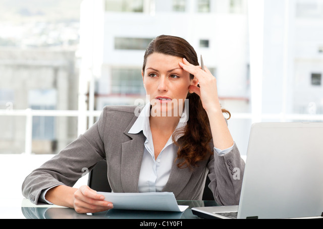 Serious female executive finding ideas while working at her desk - Stock Image