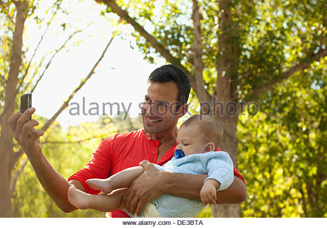 Father taking picture of himself and baby - Stock Image