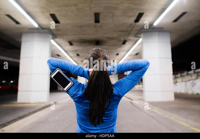 Young runner under the bridge in the evening, resting - Stock Image