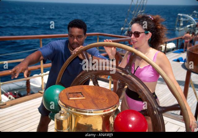 Venezuela Barefoot Windjammer SV Fantome passenger steering helm Black man crew schooner cruise woman - Stock Image