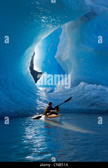 Sea kayaker on Mendenhall Lake with big blue iceberg in the background, Southeast Alaska, Summer - Stock Image