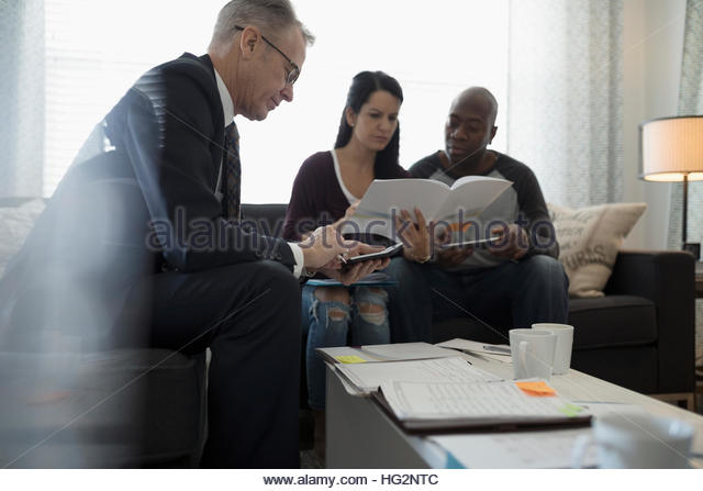 Financial advisor with calculator meeting with couple reviewing paperwork in living room - Stock Image