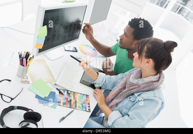 Two artists working on computer at the office - Stock Image