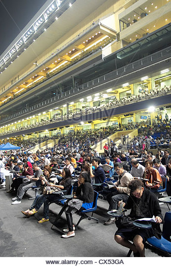Crowds of spectators in grandstand at horse racing in Happy Valley stadium in Hong Kong - Stock Image