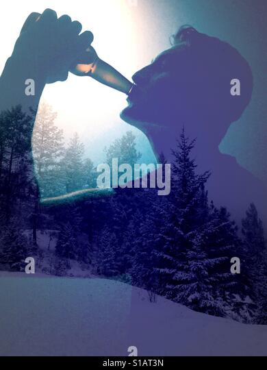 Double exposure image of young man drinking a cold beverage from a bottle and snow covered trees. - Stock-Bilder