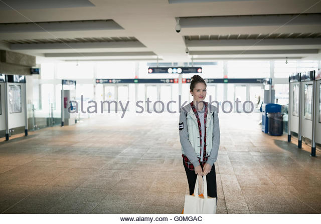Portrait teenage girl reusable shopping bag train station - Stock Image