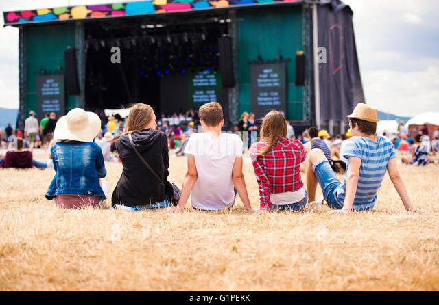 Teenagers, summer music festival, sitting in front of stage - Stock Image