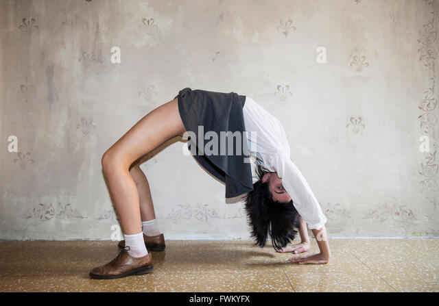 Full Length Of Woman Practicing Yoga Against Wall - Stock Image
