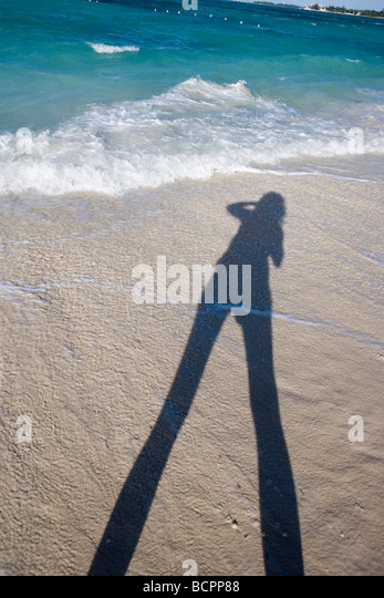a person holding a camera and taking a picture on the beach, gold sand and bright blue water - Stock Image