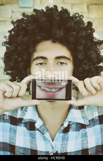 Boy smiling through a mobile phone - Stock Image