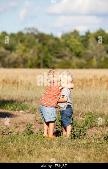 Sweden, Gotland, Havdhem, Boy and girl (2-3) hugging - Stock Image