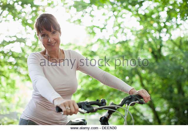 Smiling woman sitting on bicycle - Stock Image