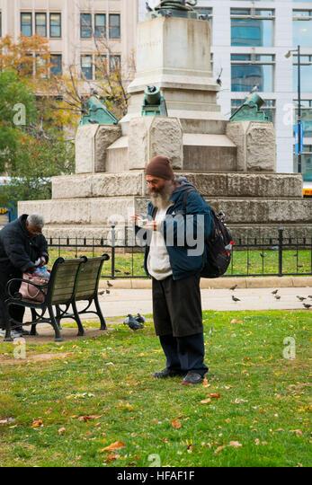 USA capital Washington DC District of Columbia old man male disheveled grey gray beard rucksack hat eating Street - Stock Image