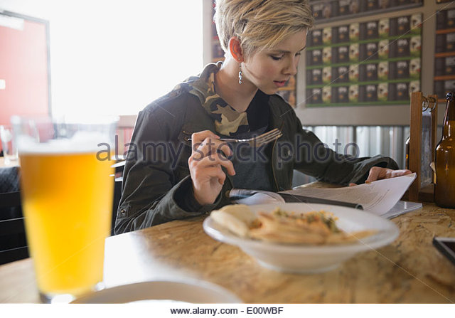 Woman with magazine enjoying lunch at brewery - Stock Image