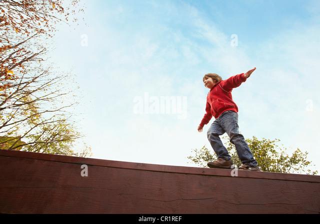 Boy balancing on wooden wall - Stock Image