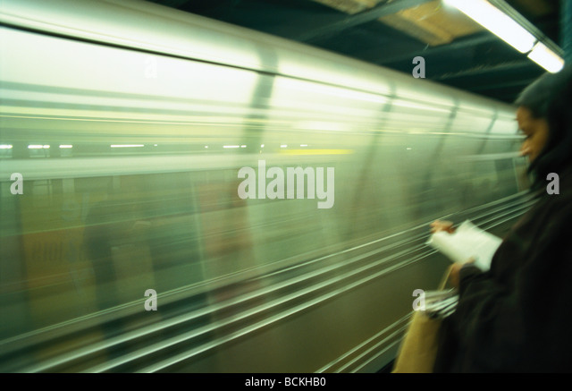 Person standing on platform reading - Stock Image