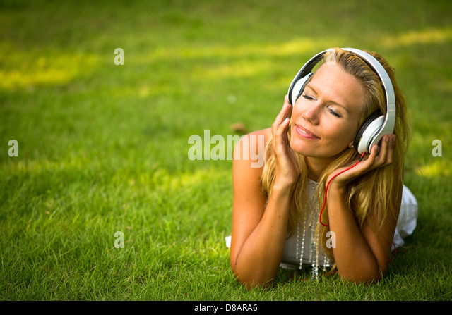 Happiness girl with headphones enjoying nature and music at sunny day. - Stock-Bilder