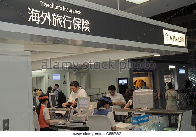 Tokyo Japan Haneda Airport kanji hiragana katakana characters symbols Japanese English travelers insurance counter - Stock Image