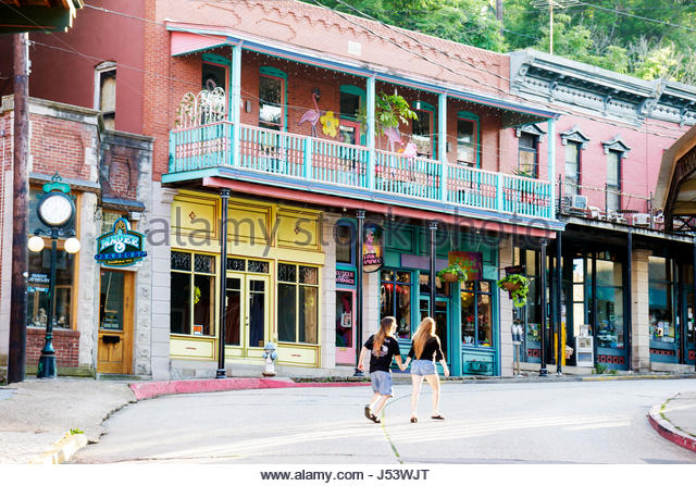 Arkansas Eureka Springs historic renovated shops couple man woman balcony store fronts short pants - Stock Image