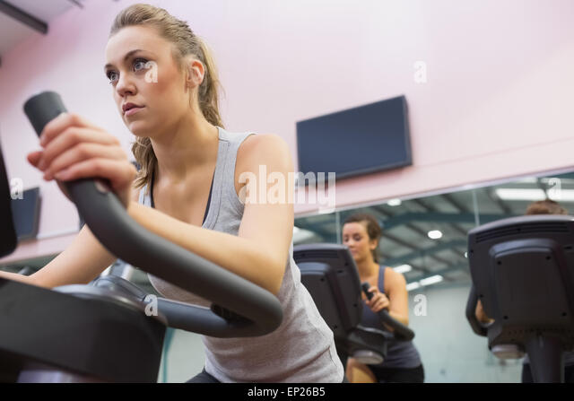 Woman training on exercise bike in a spinning class - Stock Image