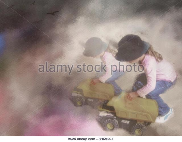a little Girl playing with a Toy truck' - Stock Image