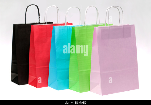 Five paper shopping bags with brights colours in a row at an angle - Stock Image