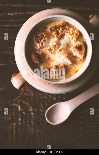 Onion soup in the ceramic pot  with spoon on the wooden table vertical - Stock Image
