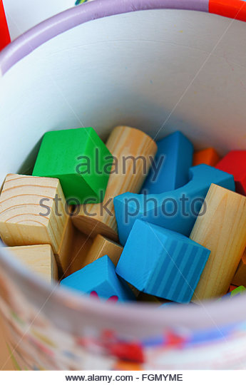Mix of toy blocks in a bucket - Stock Image