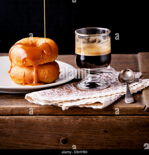Donuts and coffee on textured background - Stock Image
