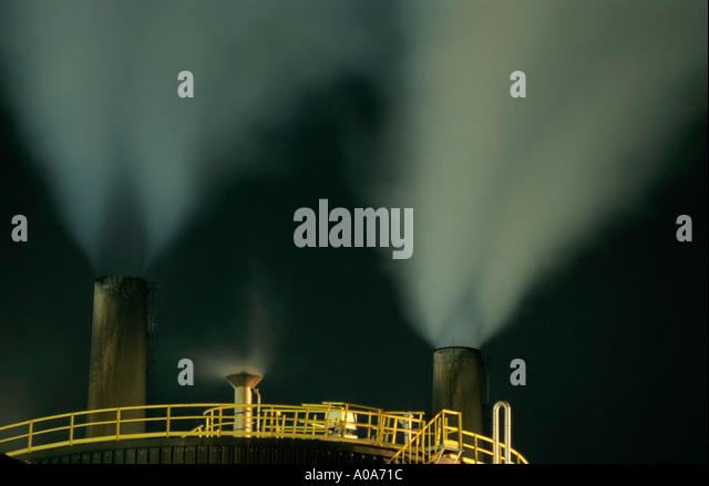 Petroleum refinery chimneys at night, France. - Stock-Bilder