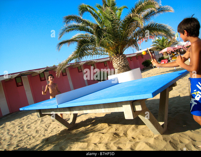 two friends playing ping-pong tennis table at the beach - Stock Image