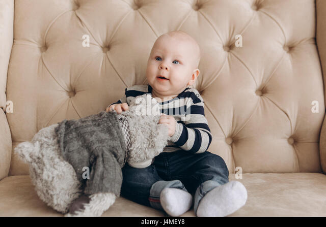 Caucasian baby boy sitting on love seat playing with teddy bear - Stock-Bilder