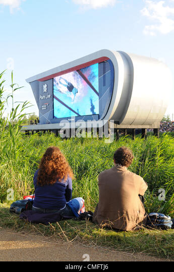 Two spectators watch the live TV coverage of the Olympics, at Park Live in the 2012 Olympic Park, London on Friaday - Stock Image