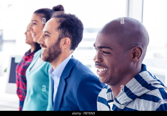 Happy business people standing in row - Stock Image