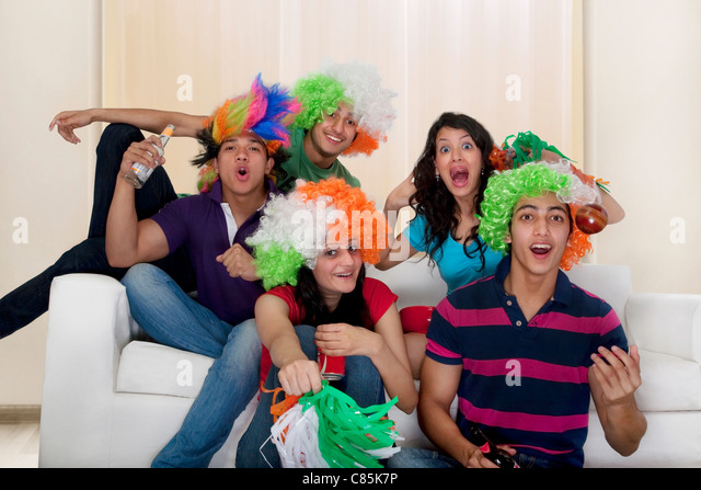 Friends watching a cricket match on tv - Stock Image