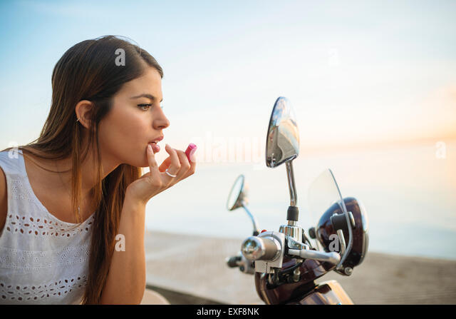 Young woman applying lipstick in motorcycle mirror, Manila, Philippines - Stock-Bilder
