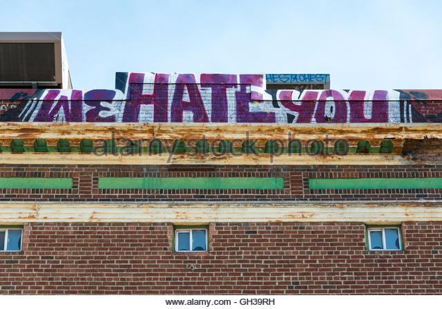 Street Vandalism: Vintage red brick wall with graffiti reading: 'We hate you'. - Stock Image