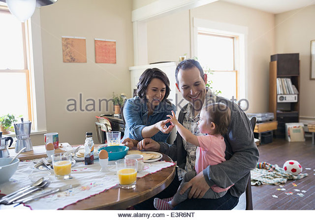 Young family enjoying breakfast at dining table - Stock-Bilder