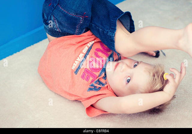 Boy on floor upside down playing with toys - Stock-Bilder