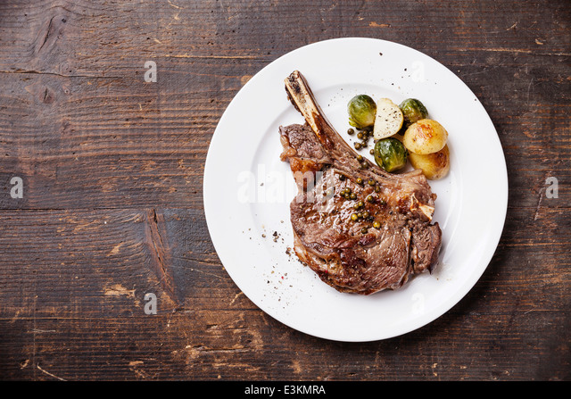 Ribeye Steak with vegetables on dark wooden background - Stock Image