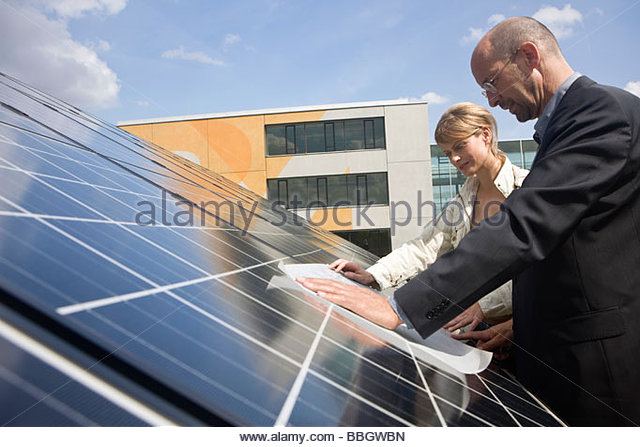 Two mature adults reading plans laid on solar panels Munich, Bavaria, Germany - Stock Image