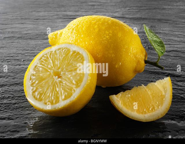 Fresh whole and cut lemons - Stock Image