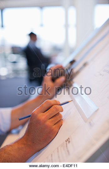 Businessman drawing on drafting table in office - Stock-Bilder