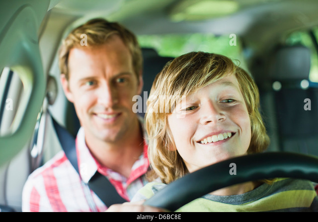 Boy driving car on fathers lap - Stock Image