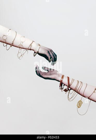 Two arms with jewelry wrapped around them - Stock-Bilder