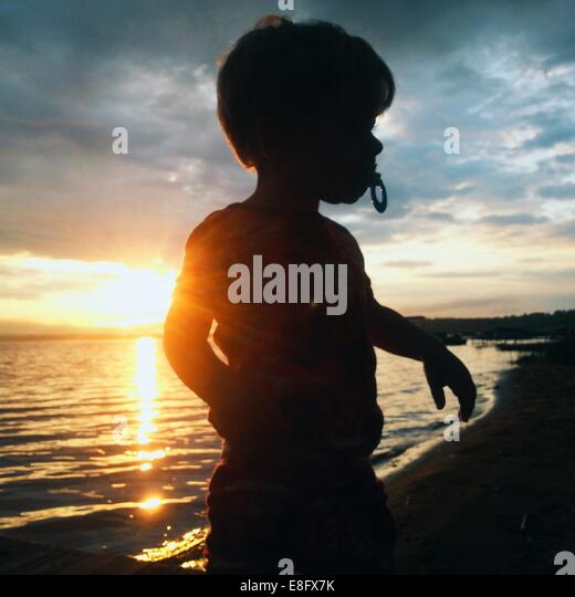 USA, Michigan, Missaukee County, Lake City, Silhouetted boy playing on beach at sunrise - Stock Image