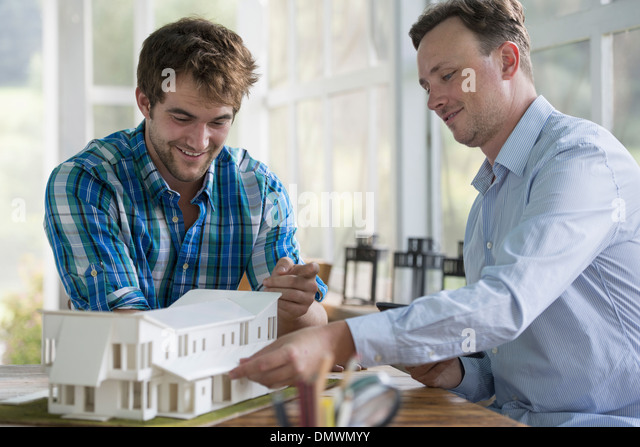 Two men looking at an architectural model of a house. - Stock-Bilder