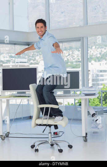 Creative designer surfing his swivel chair - Stock Image