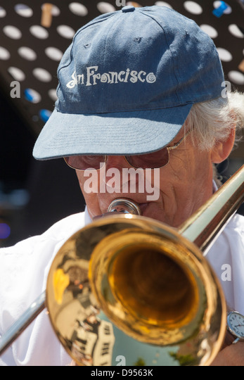 close up of male trombone player in baseball cap - Stock Image